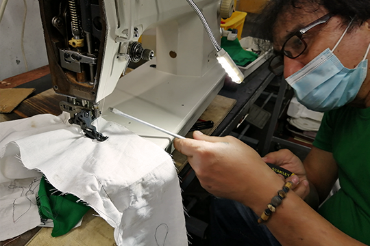 KCEI Specialist repairing an industrial sewing machine for a client